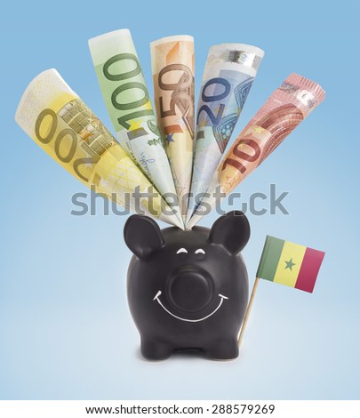 Ten,twenty,fifty,one hundred and a 200 Euro banknote in a smiling piggybank of Senegal.(series) - stock photo