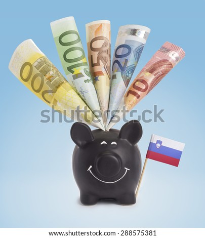 Ten,twenty,fifty,one hundred and a 200 Euro banknote in a smiling piggybank of Slovenia.(series) - stock photo