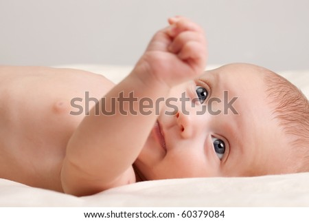 Ten weeks old cute little baby girl toddler with curious look on her face lying comfortably on bed