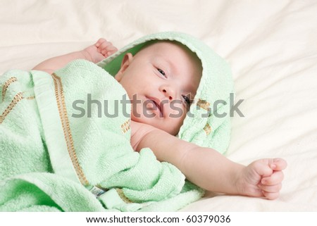 Ten weeks old cute little baby girl toddler wrapped in towel stretching her arm