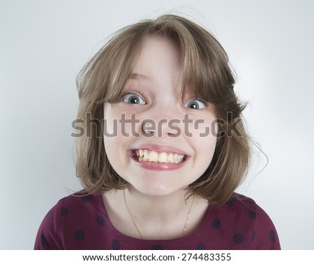 Ten-year girl with a funny smile.  - stock photo