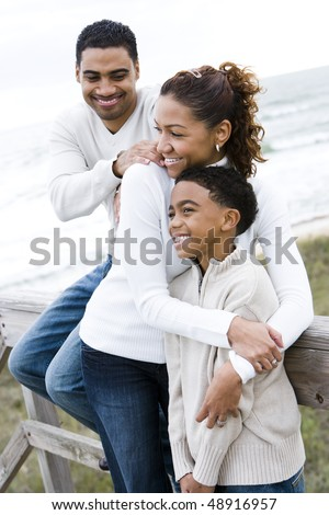 Ten year old African-American boy with parents at beach - stock photo