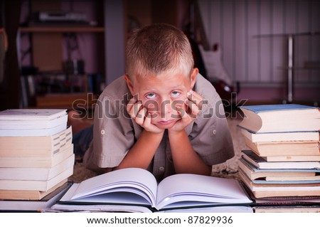 ten year old boy reading book, tired of learning process - stock photo