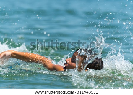 Ten year old boy teenager swims in the sea with big splashes - stock photo