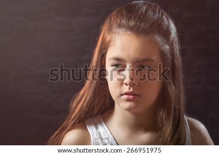 Ten year old caucasian girl with long hair posing in the studio - stock photo