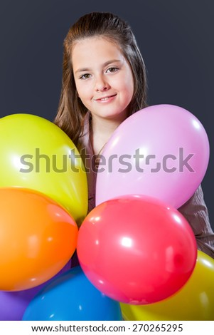 Ten year old caucasian girl with long hair posing in the studio with ballons - stock photo