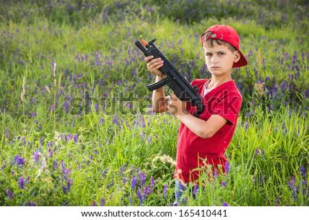 Ten year old child with toy shotgun outdoor - stock photo