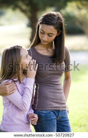 Ten year old girl whispering to her older teenage sister while walking outdoors - stock photo