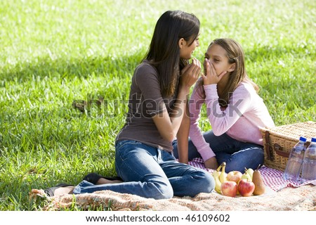 Ten year old girl whispering to teenage sister while enjoying picnic in the park - stock photo