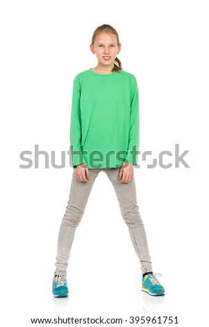 Ten Years old blond girl in green blouse, jeans and sneakers standing legs apart and looking at camera. Full length studio shot isolated on white.