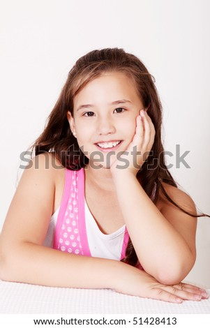 Ten years old girl sitting and looking at the camera - stock photo