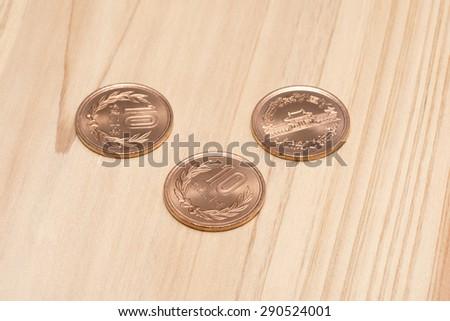 ten yen on wooden table - stock photo