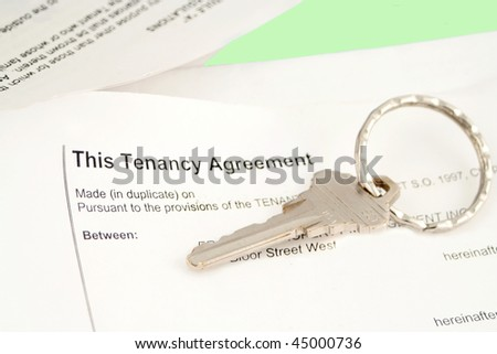 Tenancy agreement with key for lease and housing - stock photo