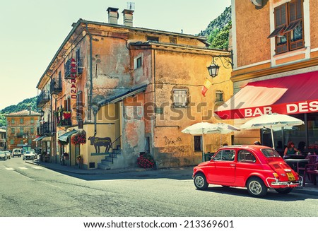 TENDE, FRANCE - AUGUST 12, 2014: Red Volkswagen beetle on the street of Tende - small town in French Alps popular with tourists and known for its cheese, honey and jams. - stock photo