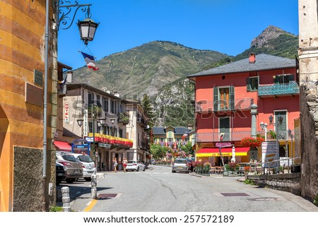 TENDE, FRANCE - AUGUST 12, 2014: Road among colorful houses in Tende - small town in French Alps located on old route of salt trade, popular with tourists and known for its cheese, honey and jams. - stock photo