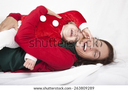 tender and funny portrait of one year age caucasian blonde cute lovely baby Santa Claus Christmas disguise with brunette woman mother red cardigan embraced laughing together lying on white - stock photo