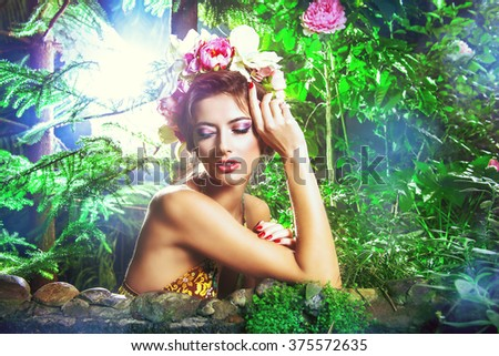 Tender beautiful girl in a flower wreath sits by a pond in the rainforest. Beauty, bodycare. Tropical vacation.  - stock photo