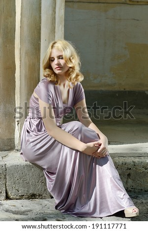 tender beautiful girl  sitting  near the column - stock photo