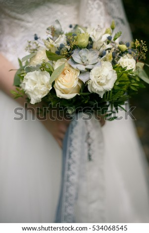 tender blue and white bouquet with lace ribbons in hands of the bride