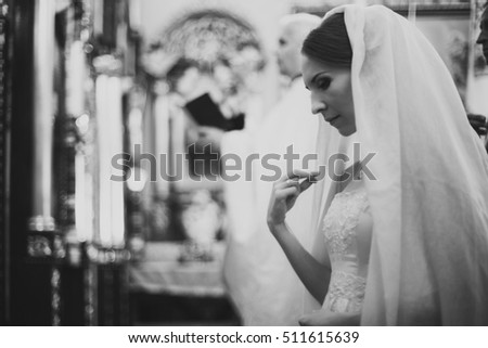 Tender bride during wedding ceremony in church
