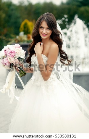 Tender bride with long dark hair and pink wedding bouquet