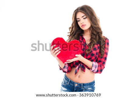 Tender charming young woman in plaid shirt and jeans shorts holding red heart over white background - stock photo