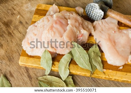 Tender chicken fillet and hammer for meat