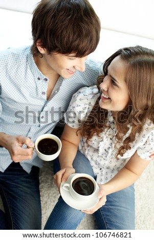Tender couple drinking coffee at home and looking at each other with affection