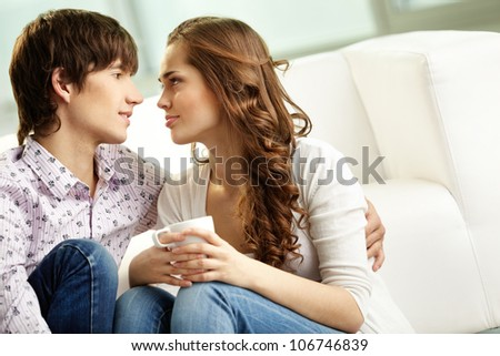 Tender couple spending time together indoors and looking at each other with affection