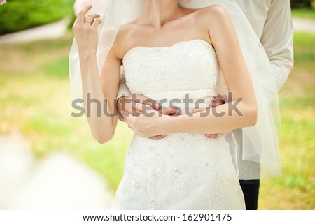 Tender embrace bride and groom - stock photo