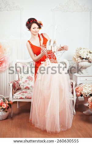 Tender girl in a red dress holding a tutu and ballet pointe shoes. Around there are flowers. - stock photo