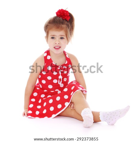 Tender girl in a red polka-dot dress and white socks is sitting on the floor - isolated on white background