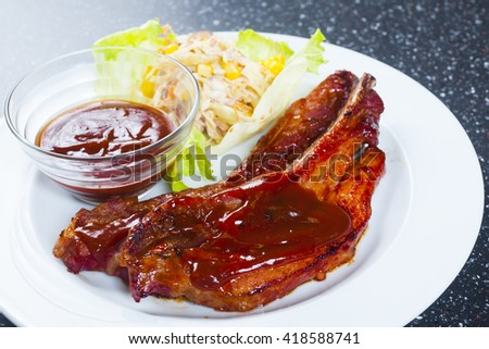 Tender grilled porterhouse or t-bone steak served with fresh green herb salad accompanied by a BBQ or tomato ketchup sauce - stock photo