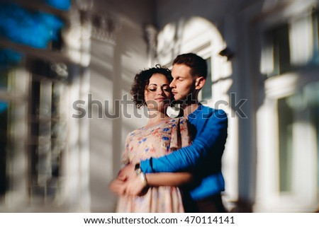 Tender hugs of a duo standing in the front of an old house