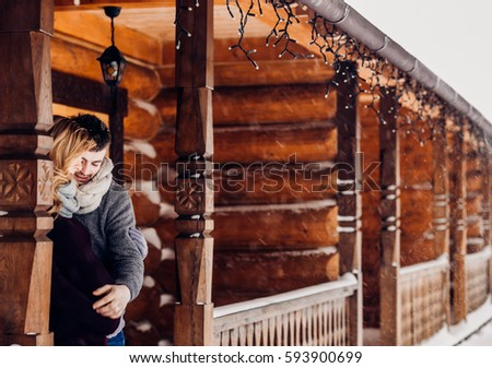 Tender hugs of expacting couple standing on wooden porch