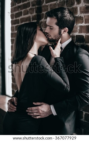 Tender kiss. Beautiful young loving couple bonding to each other and kissing while both standing against brick wall indoors - stock photo