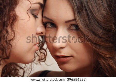 Tender kiss of two brunettes Homosexuality Lesbians studio