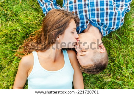 Tender kissing. Top view of a young couple in love lying together on the grass and kissing - stock photo