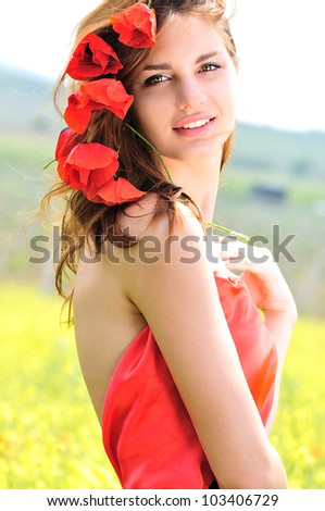 tender lady standing with poppies in her hair