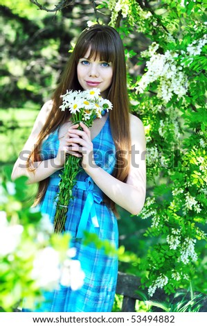 tender longhaired girl holding bunch of daisies and standing near acacia