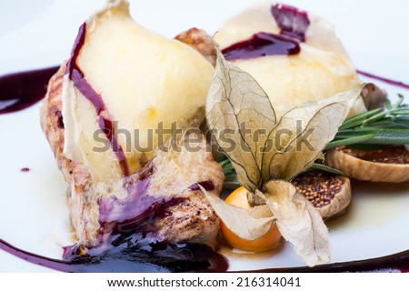 Tender medallions of pork seasoned with sweet sauce with melted slice of brie cheese, fresh figs, winter cherry and a sprig of rosemary. - stock photo