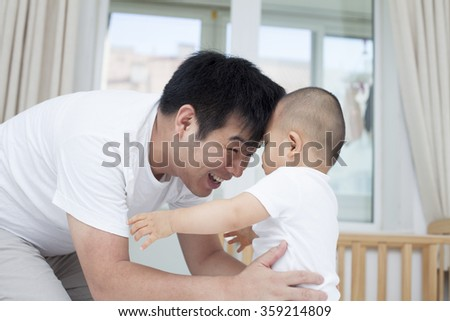 Tender moment between real Chinese father and son - stock photo