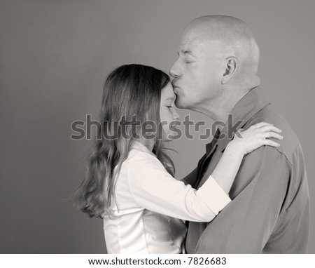 Tender Moment with Father Kissing Daughter on Forehead - stock photo