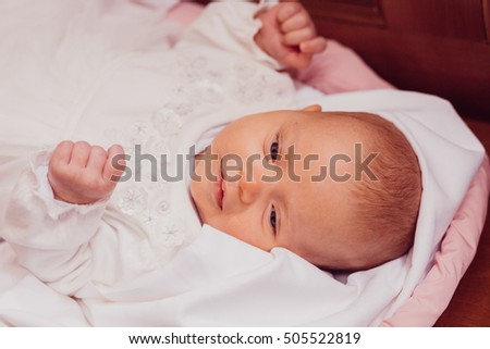 Tender newborn baby opens it eyes while lying on white pillow