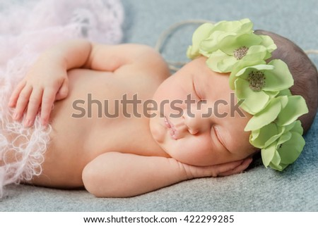 tender newborn baby sleeping with wreath on head on blanket - stock photo