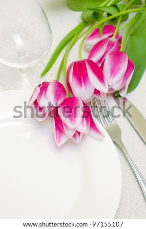 Tender pink tulips grace a table setting . Sample copy space provided with the empty white plate - stock photo