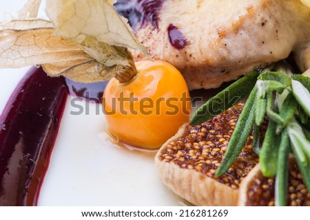 Tender pork steak medium rare seasoned with sweet sauce with melted slice of brie  cheese, fresh figs, winter cherry and a sprig of rosemary. - stock photo