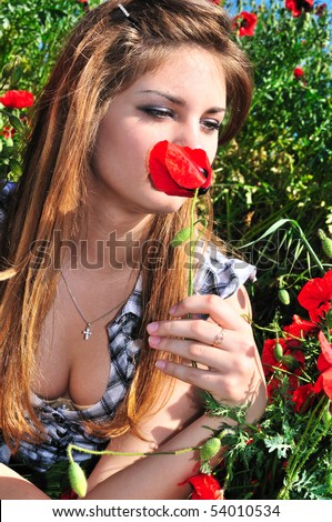 tender pretty teen girl smelling red poppy