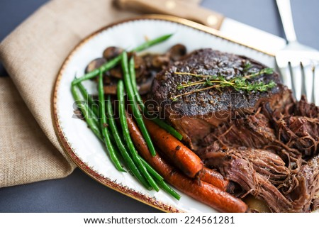 Tender roast beef with carrots and green beans on a white porcelain platter with a gold rim and serving fork against a gray tablecloth.  - stock photo