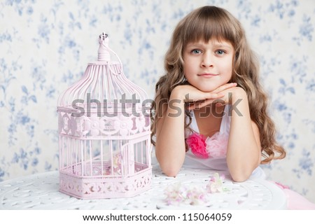 Tender sincere dreamy romantic openhearted blond girl with long wavy hair looking at camera seating near open empty pink birdcage and lacy white table on the light blue flower background - stock photo